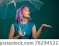 Unusual violet haired woman stands under umbrella blue in studio. Concept of fashionable girl 76294522