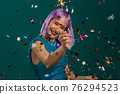 Hipster woman with sparkling bengal fire dancing under confetti rain on green background. Christmas 76294523
