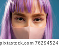 Young hipster woman in protective mask. Close-up portrait of fashion model with dyed violet 76294524
