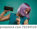 Trendy woman with dyed purple hair listening to music by wireless portable speaker - modern sound 76294526