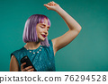 Unusual woman with dyed violet hairstyle listening to music by wireless portable speaker - modern 76294528