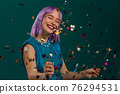 Hipster woman with sparkling bengal fire dancing under confetti rain on green background. Christmas 76294531