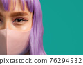 Young hipster woman in protective mask. Close-up portrait of fashion model with dyed violet 76294532