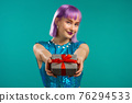 Woman with violet hair gives gift box by hands to camera on blue studio background. Girl smiling 76294533