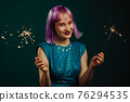 Hipster woman with sparkling bengal fire on green background. Christmas holiday concept. Young dyed 76294535