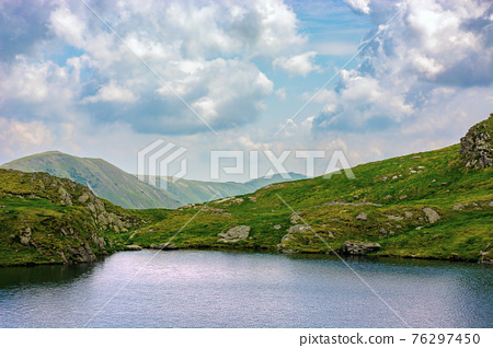 summer landscape with lake on high altitude. beautiful scenery of fagaras mountain ridge in summer. open view in to the distant peak beneath a fluffy clouds. Capra lacul, Romania 76297450