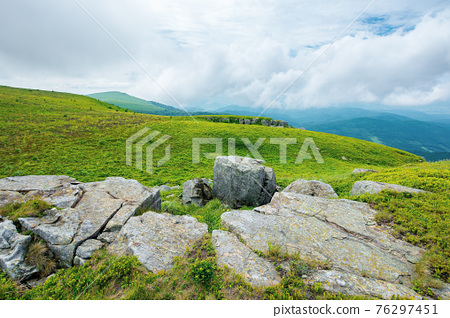 alpine mountain scenery in summer. cloudy weather. stones and boulders on grassy hills and meadows. beautiful view in to the distance 76297451
