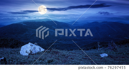 carpathian summer mountain landscape at night. beautiful countryside with rock on the grassy hill. view in to the distant valley in full moon light. clouds on the blue sky 76297455