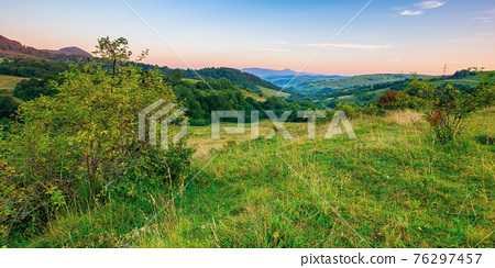 mountainous rural landscape at dawn. beautiful scenery with forests, hills and meadows in morning light. ridge with high peak in the distance. village in the distant valley 76297457