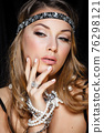 Perfect beauty and jewelry concept. Portrait of beautiful female model wearing ring, necklace and wristband on black background. Young blond woman shows glamorous finery 76298121