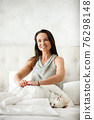 Lazy morning concept. Beautiful happy woman wakes up in bed and streches hands. Attractive female resting at home in bedroom. Little dog sleeps near on white sheets. 76298148