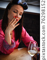 Alcoholism problem concept. Sad middle aged woman in stress sits in the kitchen, drinks white wine from a glass and smokes a cigarette. A depressed female is addicted to alcohol at home. 76298152