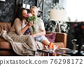 Mother and daughter relationship concept. A teenage girl congratulates happy woman on her birthday and gives her flowers and gift. The family celebrates anniversary or mother s day at home. 76298172