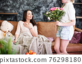 Mother and daughter relationship concept. A teenage girl congratulates happy woman on her birthday and gives her flowers and gift. The family celebrates anniversary or mother's day at home. 76298180