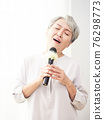 Happy senior asian woman singing with microphone. 76298773