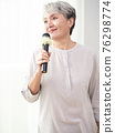 Happy senior asian woman singing with microphone. 76298774
