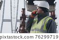 Male engineer examining bridge and speaking on cellphone 76299719