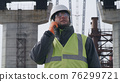 Male engineer examining bridge and speaking on cellphone 76299721