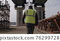 Male engineer walking under bridge 76299728