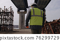 Male engineer walking under bridge 76299729