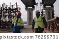 Male builders walking under bridge 76299731