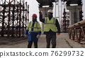 Male builders walking under bridge 76299732