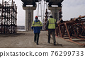 Male workers walking and discussing bridge construction 76299733