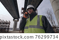Male contractor speaking on smartphone 76299734