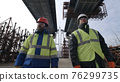 Male builders walking under bridge 76299735