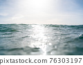 Breaking Waves and spray, white water and light reflected on the surface of the water 76303197