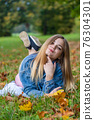 A young girl lies on the grass in a warm autumn in the evening with a petal in her hands. 76304301