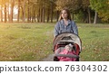 A young mother with a stroller walks in the autumn evening. 76304302