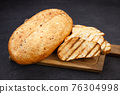 Freshly baked sliced wheat bread on cutting board 76304998
