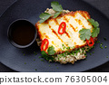 Grilled haloumi cheese on a black plate 76305004
