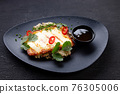 Grilled haloumi cheese on a black plate 76305006