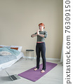 Young woman coach doing meditative asanas in 76309150