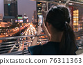 Woman clicking city picture in phone 76311363