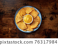Nacho chips with a cheese dip, overhead shot 76317984