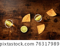 Tequila with lime and nacho chips, overhead flat lay shot 76317989