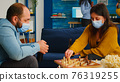 Friends with masks relaxing playing chess while drinking beer 76319255