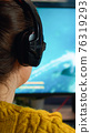 Back view of professional online gamer woman playing shooter game 76319293