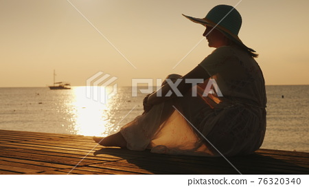 Side view: A woman sits on a wooden pier, meets the dawn by the sea. A ship is visible in the distance. Dreams and trips concept 76320340