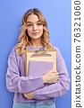 Shy teen student girl hold books isolated on pastel blue background studio portrait 76321060