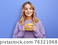 cute positive girl drinking coffee or tea in morning before school or university 76321068