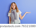 portrait of caucasian woman presenting something, showing open hand palm with copy space for product or text 76321080