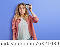 Tired woman with alarm clock attached to head 76321089