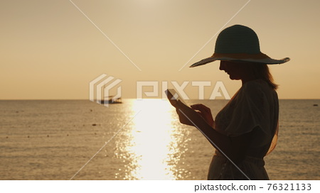 Silhouettes a young woman in a wide-brimmed hat that uses a tablet against the backdrop of a beautiful sunrise on the seashore 76321133