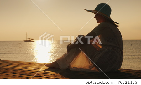 Side view: A woman sits on a wooden pier, meets the dawn by the sea. A ship is visible in the distance. Dreams and trips concept 76321135