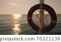 Lifebuoy hanging on the background of the sea at sunrise. Morning at the sea 76321136