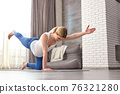 pregnant woman doing exercises for warm-up legs and arms 76321280